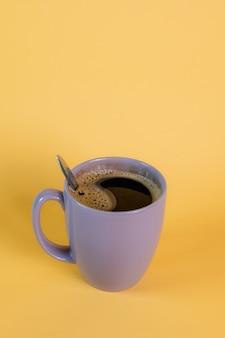Фиолетовая кружка с горячим черным кофе с несколькими пузырьками на желтом фоне, снятая в студии.