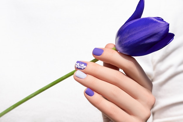Purple nail design. female hand with purple manicure holding tulip flower