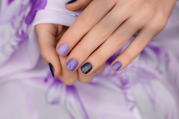紫色のネイルデザイン。紫色の手入れされた女性の手