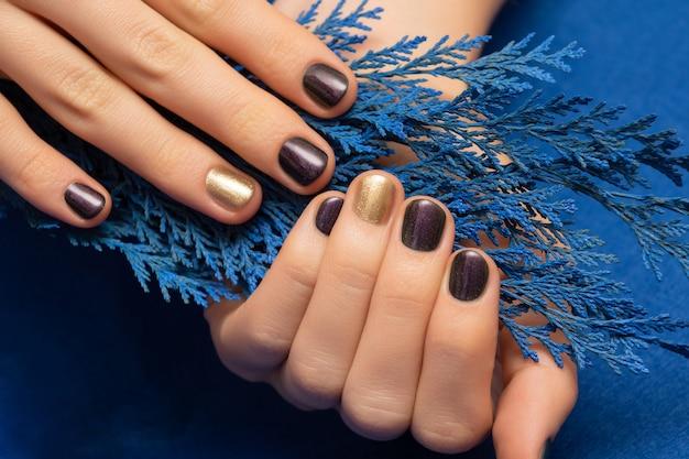 ゴールドがアクセントのパープルネイルデザイン。手入れの行き届いた女性の手。