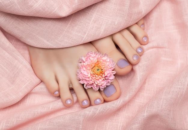 Purple nail polish pedicure on pink fabric surface.
