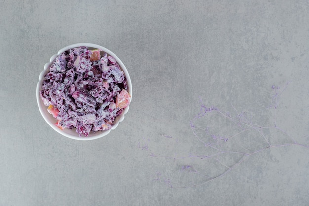 Purple onion salad in a ceramic cup on concrete surface