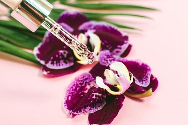 Фиолетовые орхидеи с косметическим натуральным маслом на розовом фоне