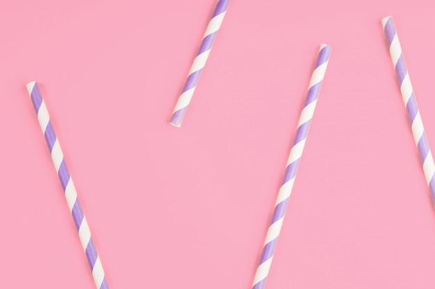 Purple paper straws on pink