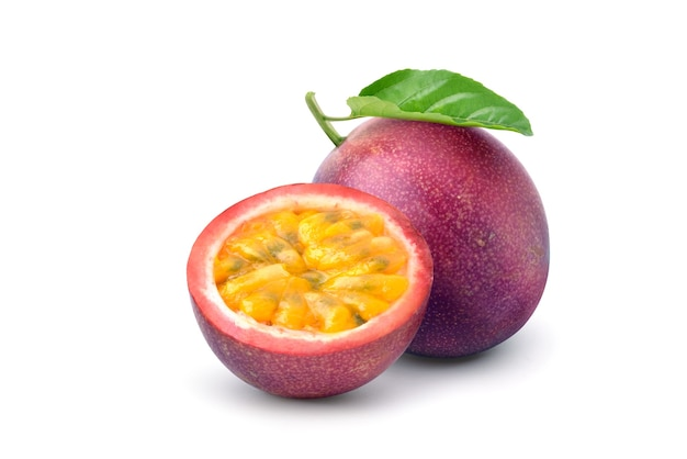 Purple passion fruit (passiflora edulis) with cut in half and green leaf isolated on white background. clipping path.