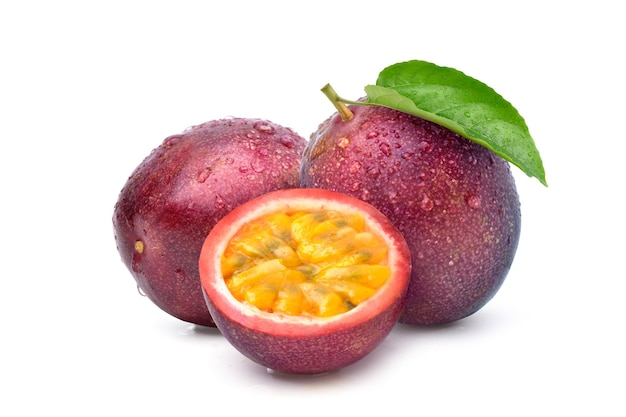 Purple passion fruit with cut in half and green leaf isolated