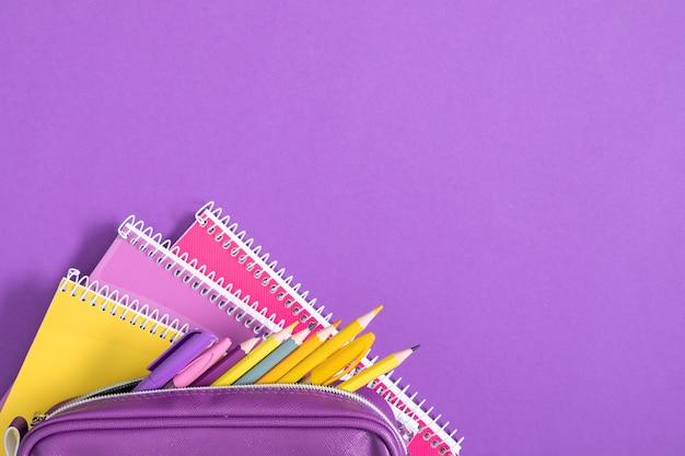 Фиолетовый пенал с карандашами и тетрадями на фиолетовом фоне обратно в школу плоская планировка