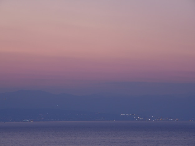Purple and pink color gradation of sunset sky over the mountain range and adriatic sea, opatija, croatia