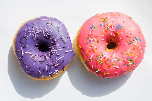 Purple and pink donuts on white background
