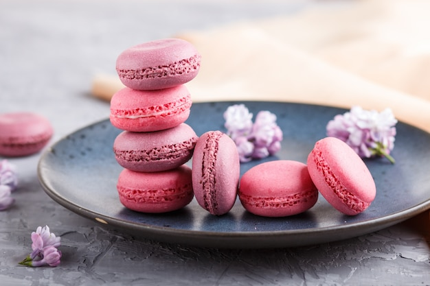 Purple and pink macaron or macaroon cakes on blue ceramic plate on gray concrete background