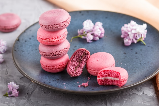 Purple and pink macaron or macaroon cakes on blue ceramic plate on gray concrete.