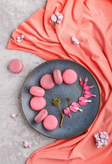 Purple and pink macaron or macaroon cakes on blue ceramic plate with red textile on gray concrete.