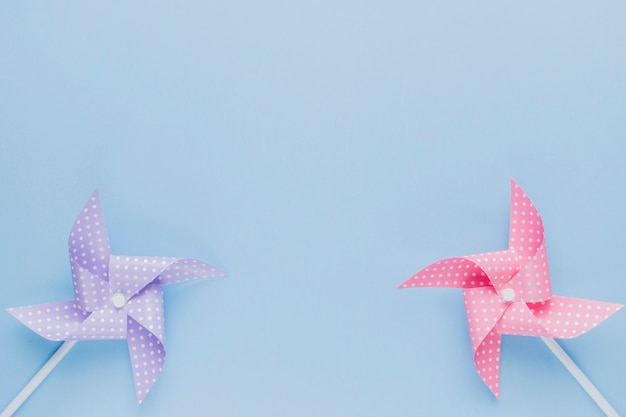 Purple and pink origami pinwheel on plain blue backdrop