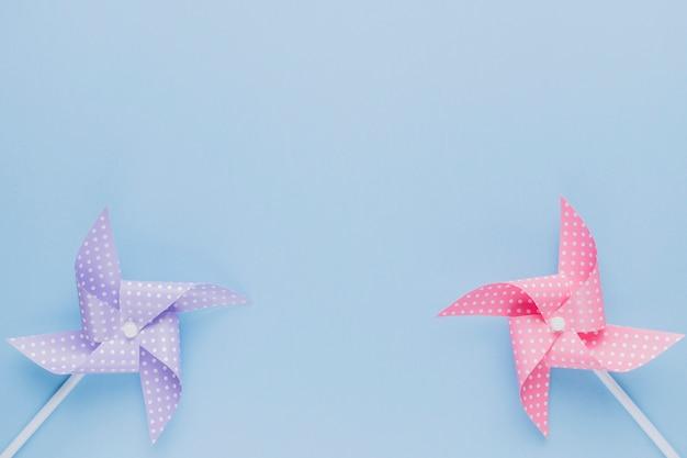 Purple and pink origami pinwheel on plain blue backdrop