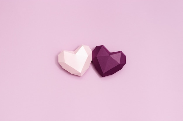 Purple and pink polygonal paper hearts together