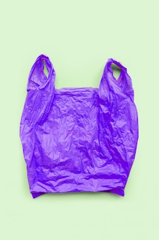 Purple plastic bag on green background. environment pollution concept.