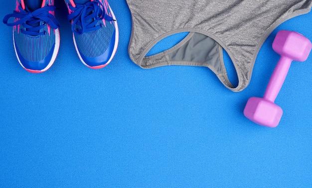 青色の背景に紫のプラスチックダンベル、灰色のスポーツシャツ