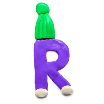 Фиолетовая пластилиновая буква p алфавита в зеленой зимней шапке на белом фоне