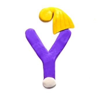 Фиолетовая пластилиновая буква y алфавита в зимней желтой кепке на белом фоне