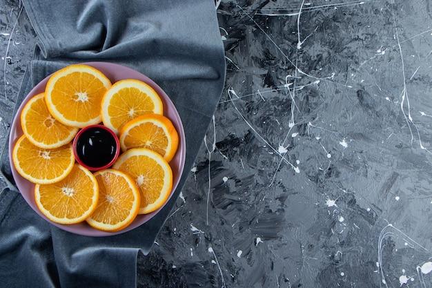 Фиолетовая тарелка нарезанных сочных апельсинов на мраморной поверхности.