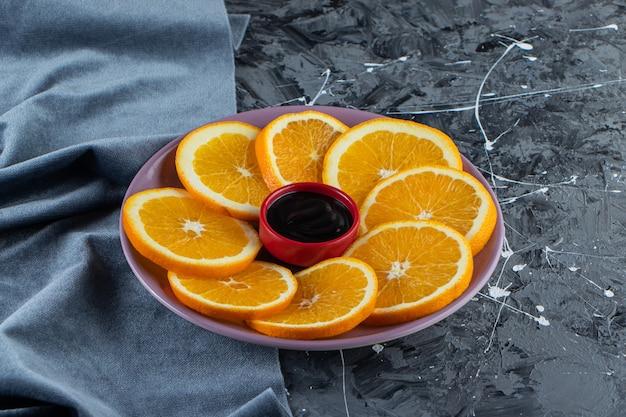 Purple plate of sliced juicy oranges on marble surface.