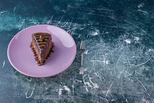 Purple plate with sliced chocolate cake on marble background.