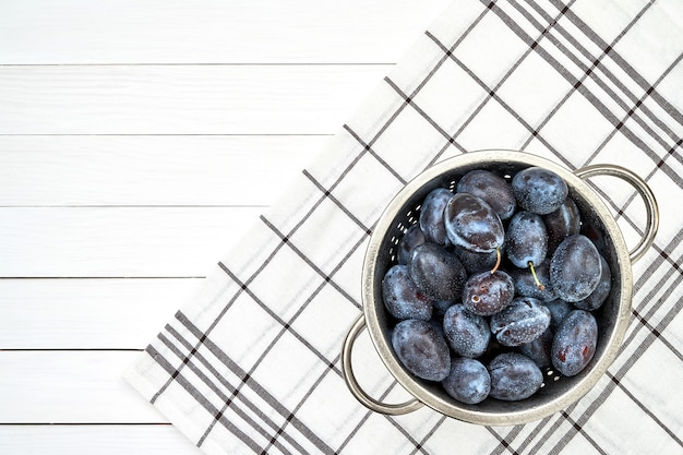 Purple plums in colander on white wooden table. top view, copy space