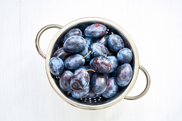 Purple plums in colander on white wooden table.