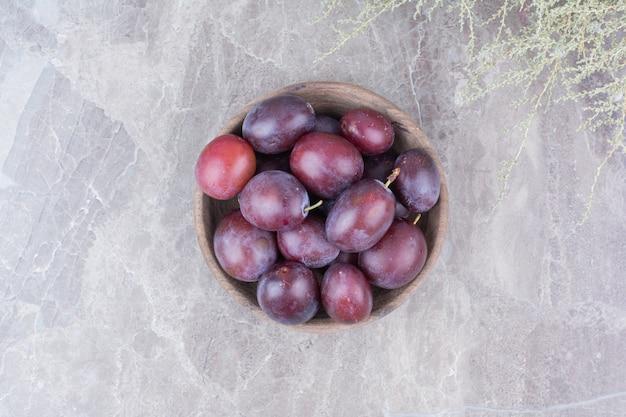 石の背景に木製のボウルに紫の梅。