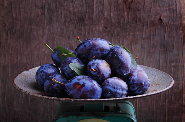 Purple plums in a metal bowl on a dark background