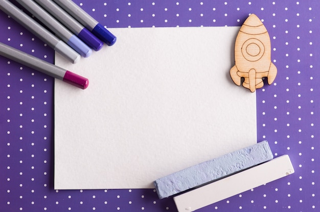 Purple polka dot desk with set of colorful pencils and blank note paper