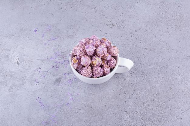 Caramella di popcorn viola servita in una tazza da tè su sfondo marmo. foto di alta qualità