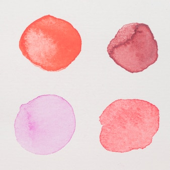 Purple, red, pink and crimson paints on white paper