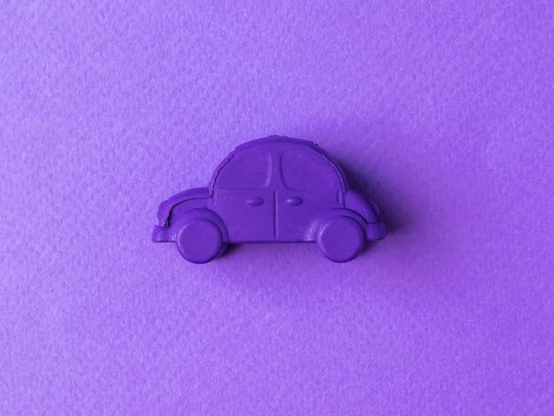 Purple retro car toy on a purple background.