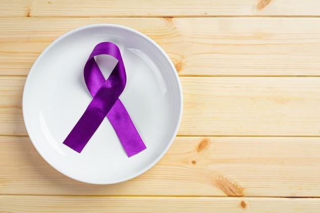 Фиолетовая лента на деревянной поверхности.