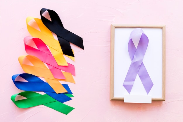 Purple ribbon on white wooden frame with the row of colorful awareness ribbon