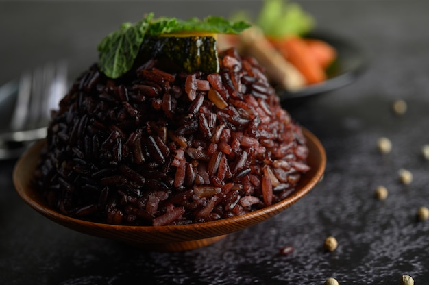Purple rice berries cooked in a wooden dish with mint leaves.