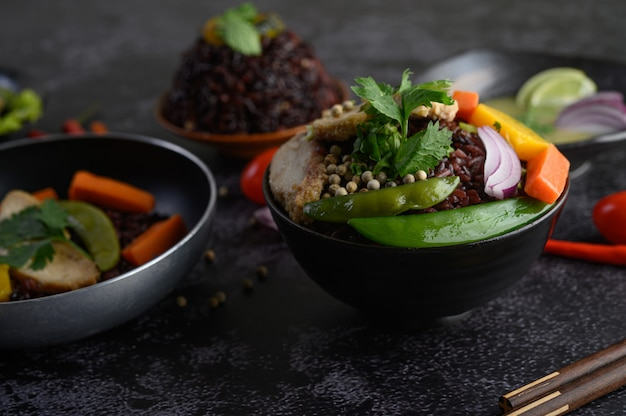 Bacche di riso viola con fagioli, carote e foglie di menta in una ciotola