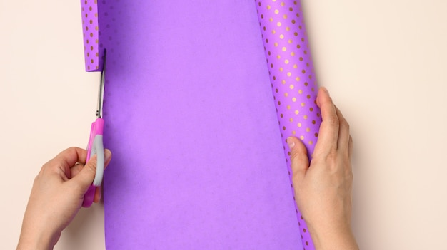 Purple roll of wrapping paper in female hands on a beige background, top view