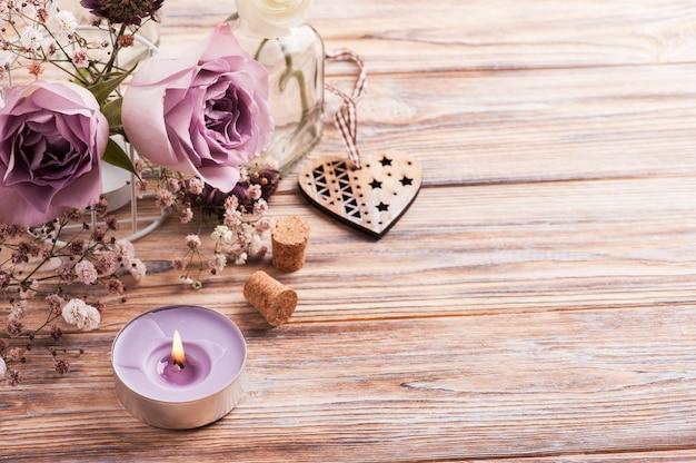 Фиолетовые розы в бутылке и зажженная свеча