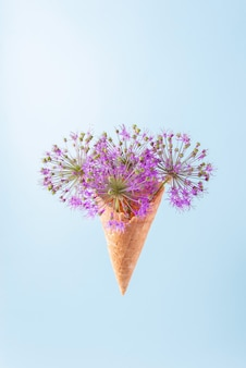 Фиолетовые круглые цветы в вафельном рожке на синем фоне