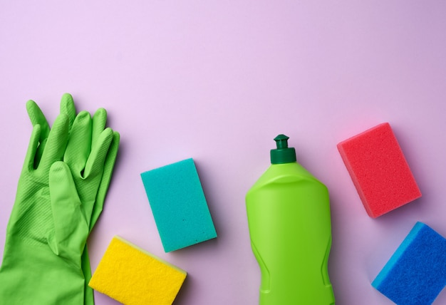 Purple rubber gloves for cleaning, multi-colored sponges, cleaning fluid in a green plastic bottle