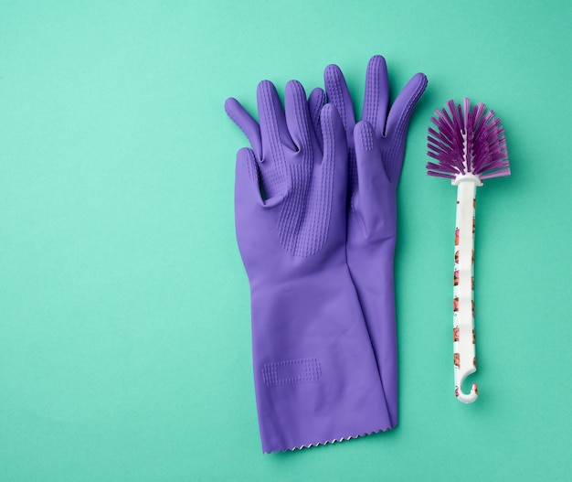 クリーニング用の紫色のゴム手袋と緑の表面に白いブラシ