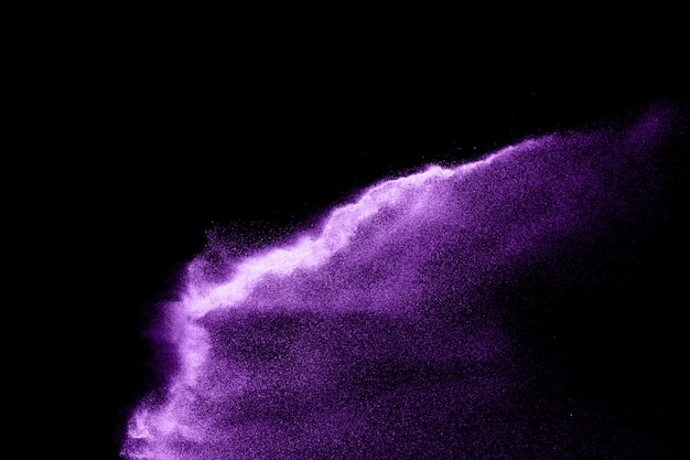 Purple sand explosion isolated on black background. abstract sand cloud.