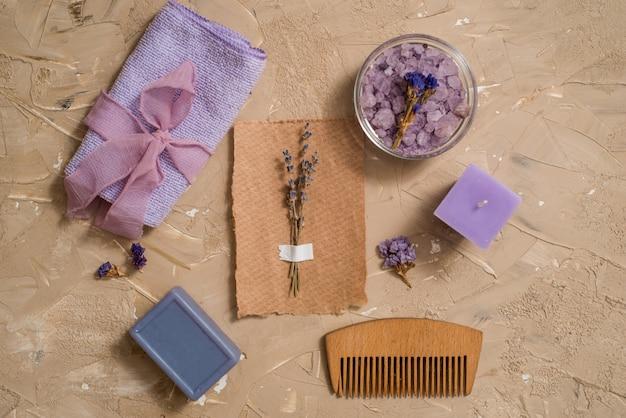 Purple sea salt, a wooden comb towel on a concrete brown background.