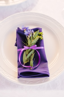 A purple serving napkin with a sprig of green leaves and a cornflower, tied with a satin ribbon, lies on a serving plate. decor banquet