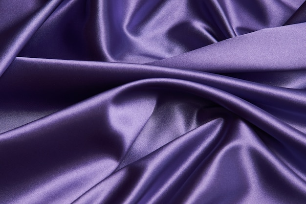Purple silk fabric background, close-up. smooth violet satin cloth texture can use as abstract background with copy space