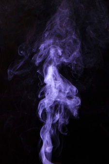 Purple smoke fragments on a black background