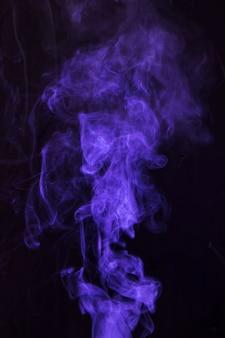 Фиолетовое движение дыма на черном фоне