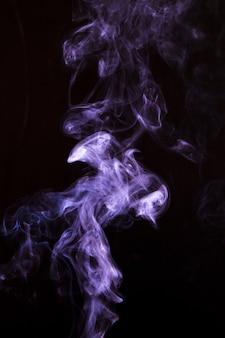 Фиолетовый дым кружится на темном фоне